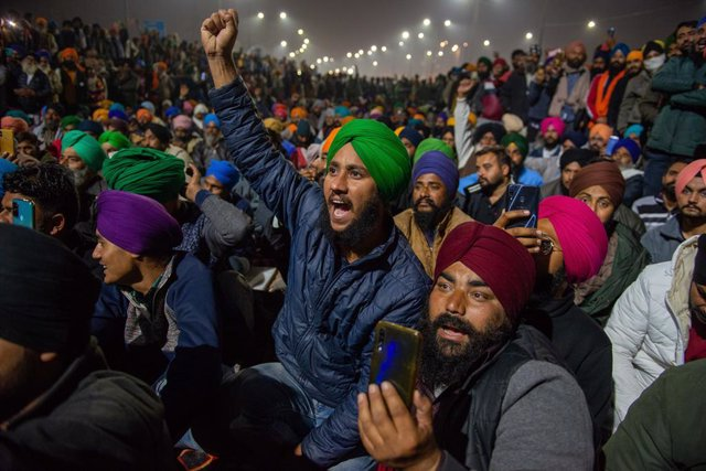 15 December 2020, India, Ghaziabad: Indian farmers listen to a speaker along a blocked highway during the ongoing sit-in protest at Singhu border against new agricultural laws. Photo: Pradeep Gaur/SOPA Images via ZUMA Wire/dpa
