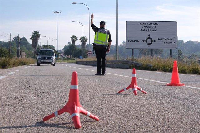 Un agente de la Policía Nacional realiza controles de movilidad a la entrada de la localidad de Manacor, Mallorca
