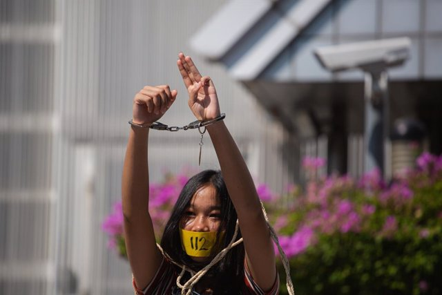 10 December 2020, Thailand, Bangkok: A protestor raises a three-finger salute with her hands in handcuffs during a rally to mark the constitution Day and International Human Rights Day. Photo: Varuth Pongsapipatt/SOPA Images via ZUMA Wire/dpa