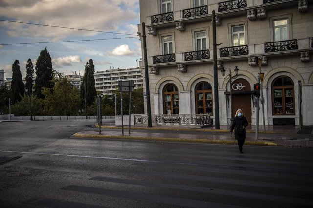 07 November 2020, Greece, Athens: A woman wearing a face mask crosses an empty street at the start of a three week national lockdown for Greece. Greek Prime Minister Kyriakos Mitsotakis said on Thursday that he has ordered the country's second lockdown to