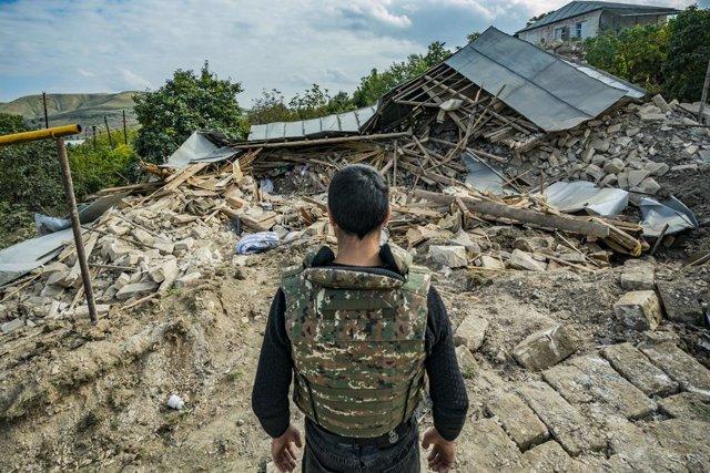 Un miliciano en las ruinas de una casa destruida en suelo armenio por los enfrentamientos de Armenia y Azerbaiyán por la región de Nagorn Karabaj