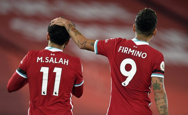 16 December 2020, England, Liverpool: Liverpool's Mohamed Salah celebrates his side's first goal with his team mate Roberto Firmino during the English Premier League soccer match between Liverpool and Tottenham Hotspur at the Anfield stadium. Photo: Peter