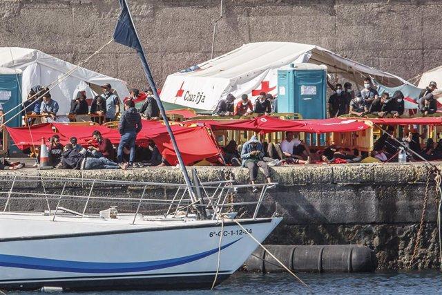 Varios inmigrantes en el Muelle de Arguineguín, en Gran Canaria, Canarias (España), a 18 de noviembre de 2020. Más de 2.300 migrantes permanecen hacinados en este muelle tras pernoctar en el campamento que se instaló el pasado mes de agosto en el recinto