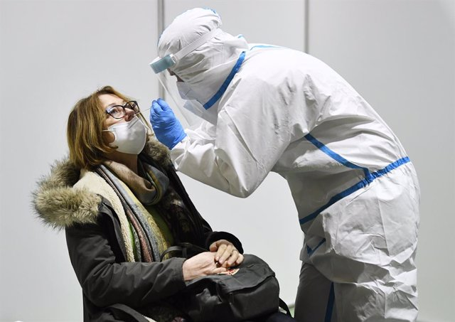 10 December 2020, Austria, Eisenstadt: A health worker takes a swab from a woman for coronavirus test at the All Sports Centre. Photo: Robert Jaeger/APA/dpa