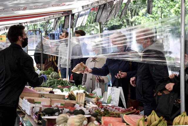 "12 May 2020, France, Paris: A salesman wearing a face mask sells vegetables and fruit from behind a protective plastic sheet at ""Place des Fetes"" market. Photo: Alain Jocard/AFP/dpa"