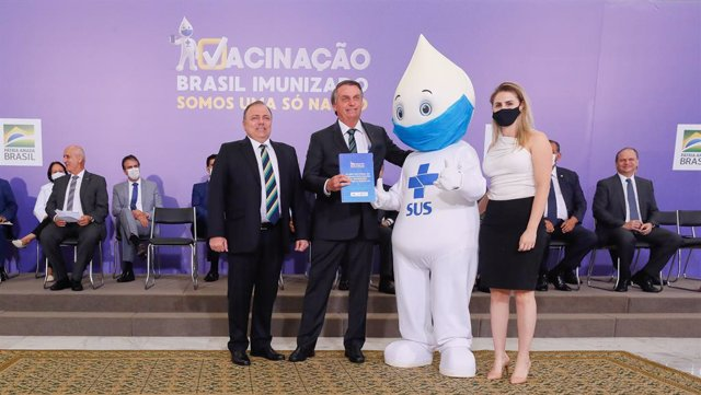 HANDOUT - 16 December 2020, Brazil, Brasilia: Brazilian President Jair Bolsonaro (2nd L) poses for a photo with the mascot Ze Gotinha, a traditional character in Brazil created to raise awareness about the coronavirus vaccines, during the launch of the Na