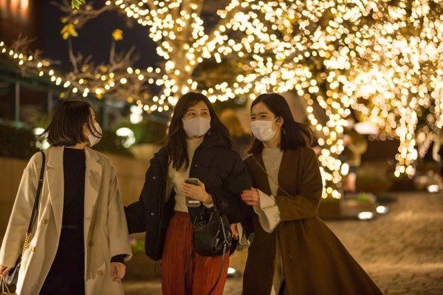 11 December 2020, Japan, Tokyo: Women wearing face masks walk down a passage with Christmas decoration in Ebisu. Photo: Stanislav Kogiku/SOPA Images via ZUMA Wire/dpa