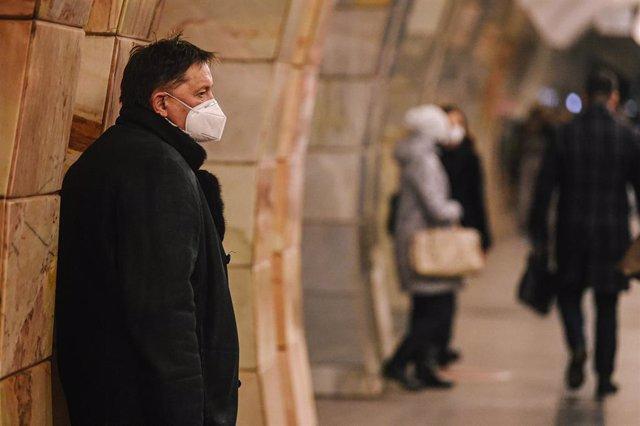 Un hombre con mascarilla esperando la llegada del metro en Moscú