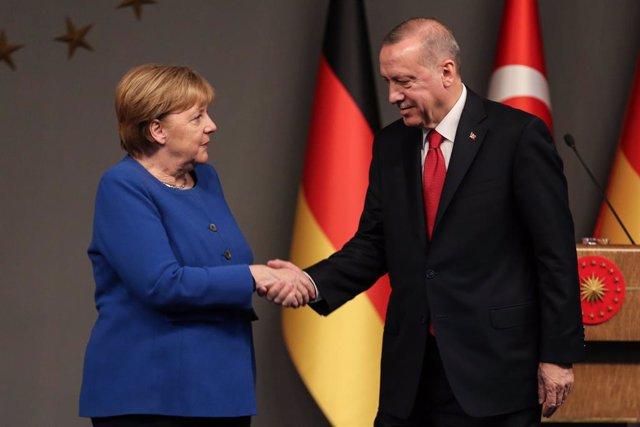 FILED - 24 January 2020, Turkey, Istanbul: Turkish President Recep Tayyip Erdogan and German Chancellor Angela Merkel shake hands after a mutual press conference. Turkish President Recep Tayyip Erdogan and German Chancellor Angela Merkel held a phone conv