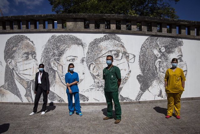 19 June 2020, Portugal, Porto: (L-R)Health workers Cristina Teixeira, Patricia Botelho, David Andrade, and Idalina Ramos, pose in front of a wall bearing their own portraits at Sao Joao hospital during the inauguration of the artwork by Portuguese artist