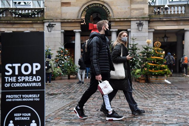 18 December 2020, England, London: People walk past a sign advising social distancing in Covent Garden. Photo: Kirsty O'connor/PA Wire/dpa