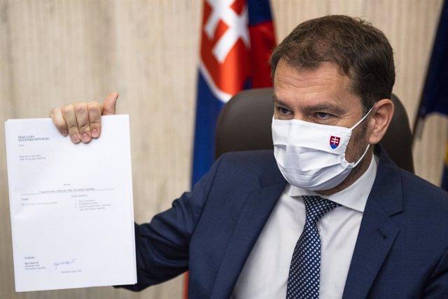 19 April 2020, Slovakia, Bratislava: Slovak Prime Minister Igor Matovic wearing a face mask as he holds a draft of the government program while its declaration during the 12th session of the Slovak government. Photo: Jaroslavnovák/TASR/dpa