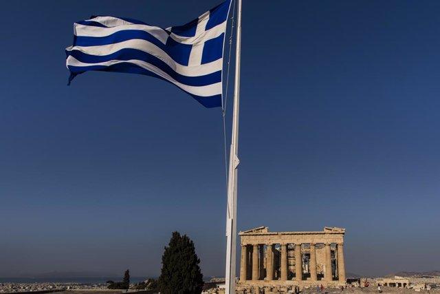 Una bandera de Grecia frente al Partenón, en Atenas