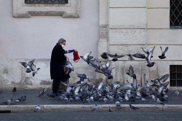 23 November 2020, Italy, Rome: A woman wearing a face mask feeds the pigeons. Photo: Cecilia Fabiano/LaPresse via ZUMA Press/dpa