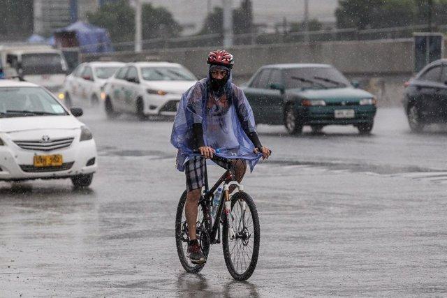 Un home circula amb bicicleta per Manila sota la pluja