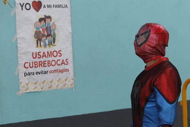 Hombre junto a un cartel de concienciación por el coronavirus en México