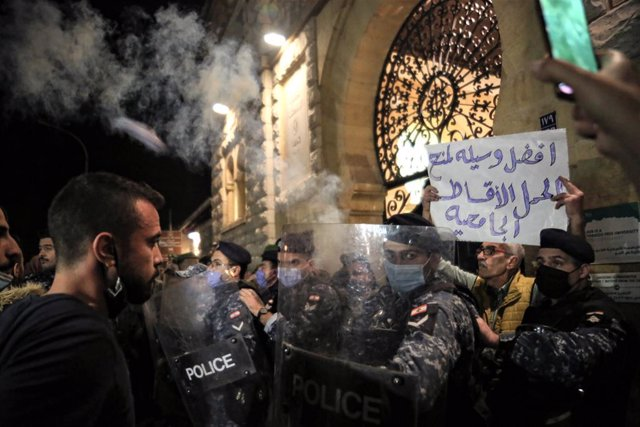 19 December 2020, Lebanon, Beirut: Anti-government activists and university students face riot police during a demonstration due to the rise of tuition fees amid an acute economic crisis and political impasse engulfing the country. Photo: Marwan Naamani/d