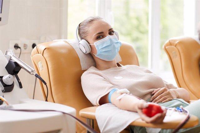 Mujer donando sangre en tiempo de coronavirus.