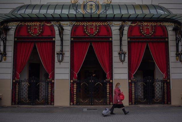 Una dona camina enfront de l'Hotel Palace a Barcelona. Foto d'arxiu.