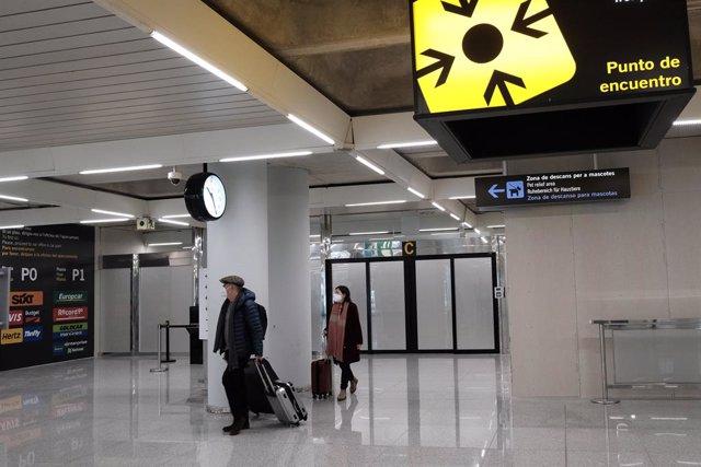 Dos personas en el aeropuerto de Palma de Mallorca (Islas Baleares), a 20 de diciembre de 2020. A partir de este domingo, los turistas nacionales que se desplacen a Baleares procedentes de la Península deberán presentar una PCR negativa realizada en orige