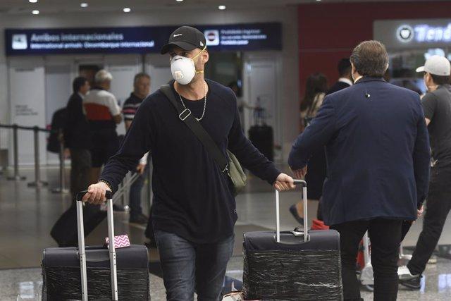 Un turista con mascarilla en un aeropuerto de Argentina por el coronavirus.