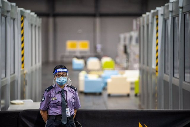 02 December 2020, China, Hong kong: A security guard wearing a face shield stands at the Covid-19 community treatment facility. Photo: Geovien So/SOPA Images via ZUMA Wire/dpa