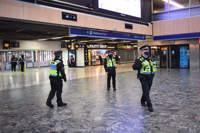 20 December 2020, England, London: Police officers walk at Euston Station, as more police forces are deployed to enforce travel rules at London's stations. British Prime Minister Boris Johnson announced a strict lockdown and cancelled Christmas holiday ga