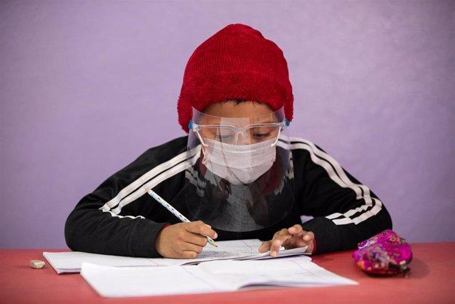 Un estudiante con mascarilla en Katmandú