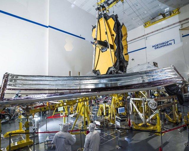 Para ayudar a garantizar el éxito, los técnicos inspeccionan cuidadosamente el parasol del telescopio espacial James Webb antes de que comience la prueba de despliegue.