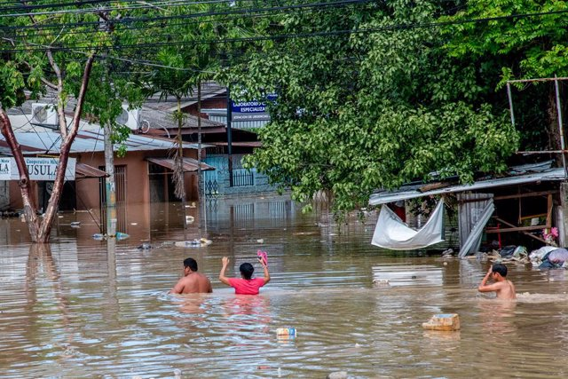 19 November 2020, Honduras, La Lima: A family wades through shoulder high floodwaters after the devastating hurricane Iota made landfall in Honduras. Photo: Seth Sidney Berry/SOPA Images via ZUMA Wire/dpa
