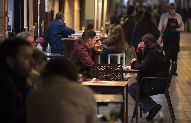 Varias personas en la terraza de un bar tras la apertura de bares y restaurantes de 20 a 22,30 horas con la flexibilización de restricciones de la Junta de Andalucía. En Sevilla (Andalucía, España), a 18 de diciembre de 2020.