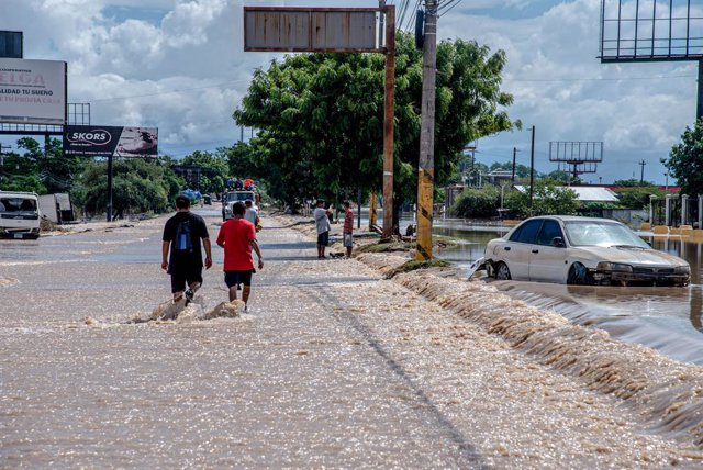 19 November 2020, Honduras, La Lima: People walk on a flooded highway after the devastating hurricane Iota made landfall in Honduras. Photo: Seth Sidney Berry/SOPA Images via ZUMA Wire/dpa
