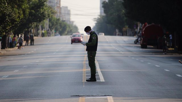 04 April 2020, Cuba, Havana: A policeman wears a face mask as he stands in a deserted street. Cuba has sealed off a part of downtown Havana popular with tourists because of the Coronavirus pandemic. Photo: Guillermo Nova/dpa