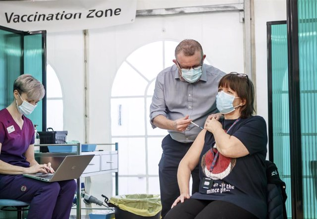 21 December 2020, England, York: Nurse practitioner York Medical Group Chris Pflueger (R) receives the Pfizer-BioNTech vaccine at a vaccination centre in York. Photo: Danny Lawson/PA Wire/dpa