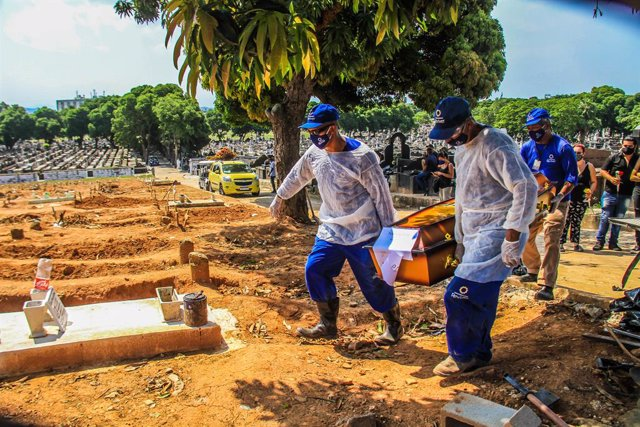 16 December 2020, Brazil, Rio de Janeiro: Relatives and medics in protective suits carry the body of a man who died from the coronavirus (COVID-19) at Sao Francisco Xavier cemetery. Photo: Ellan Lustosa/ZUMA Wire/dpa