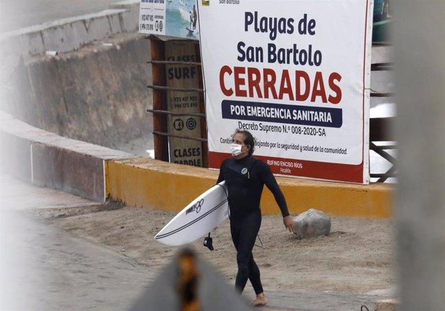 Un surfista en una playa de Lima, Perú, en pleno confinamiento por la crisis del coronavirus.