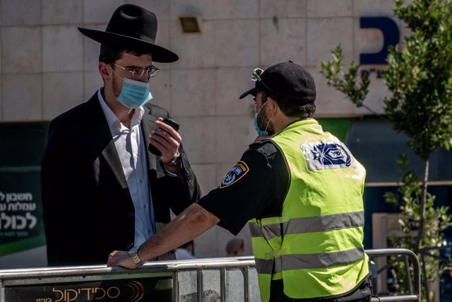 Un policía de Israel junto a un hombre durante la pandemia de coronavirus