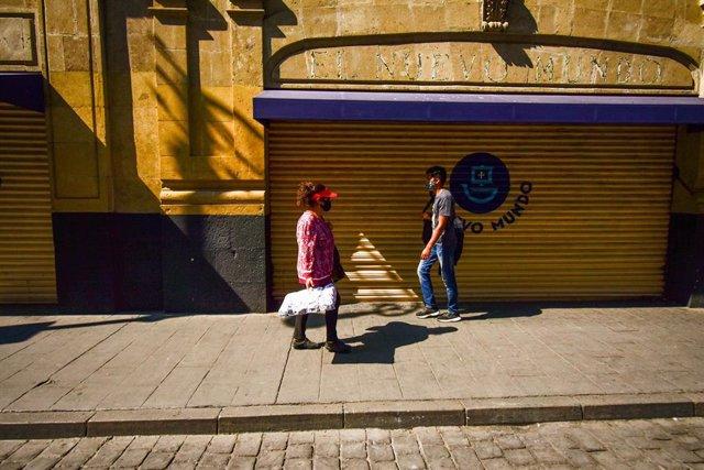 Personas caminando frente a un negocio cerrado en México en el contexto de la pandemia de coronavirus.