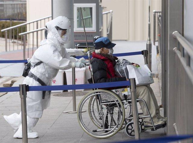 Personal médico traslada a un paciente con coronavirus a las instalaciones de un hospital de Seúl, Corea del Sur.