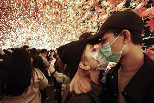 18 December 2020, Taiwan, New Taipei City: A couple wear face masks as they kiss in an autumn leaves decoration at the foot bridge before the Christmas. Photo: Daniel Ceng Shou-Yi/ZUMA Wire/dpa