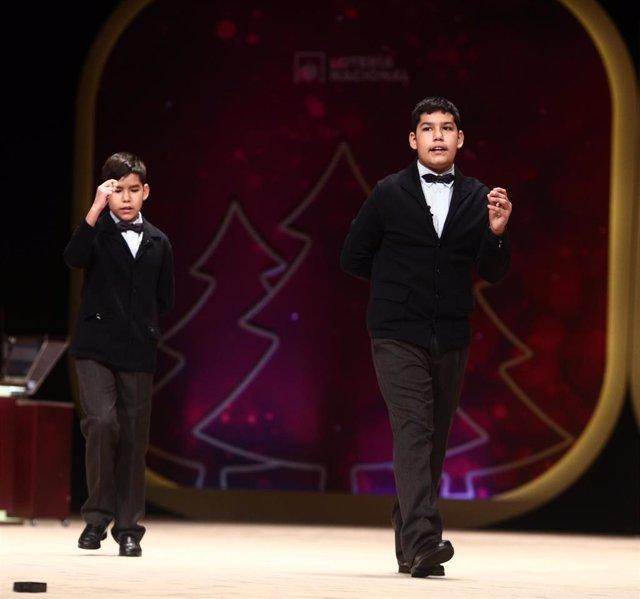 Dos de los niños de la residencia de San Ildefonso, Alonso Dávalos Durán (i) y Samuel Dávalos Durán (d) cantan dos de los quintos premios de la Lotería de Navidad, el `19371 y el `49.760 durante la celebración del Sorteo Extraordinario de la Lotería de