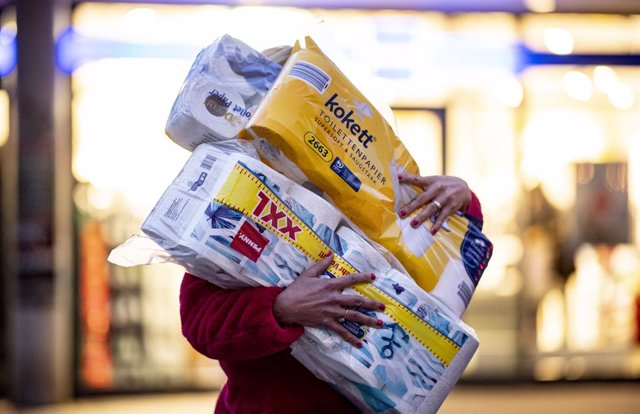 FILED - 05 November 2020, Hamburg: A woman walks out of a drug store with rolls of toilet paper during a wave of panic buying amid the coronavirus pandemic. Photo: Axel Heimken/dpa