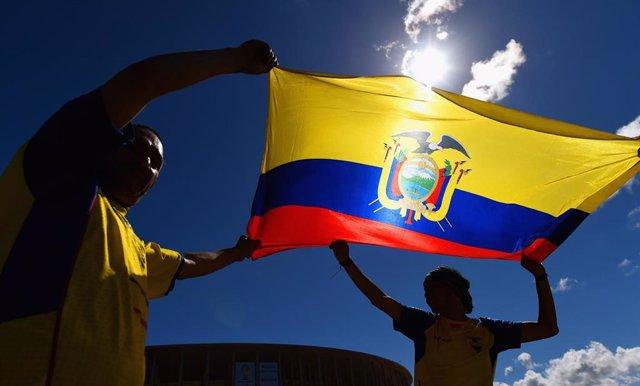 Dos hombres sosteniendo la bandera de Ecuador.