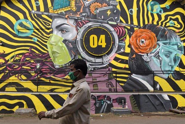 Un hombre con mascarilla pasa ante un mural en Bombay