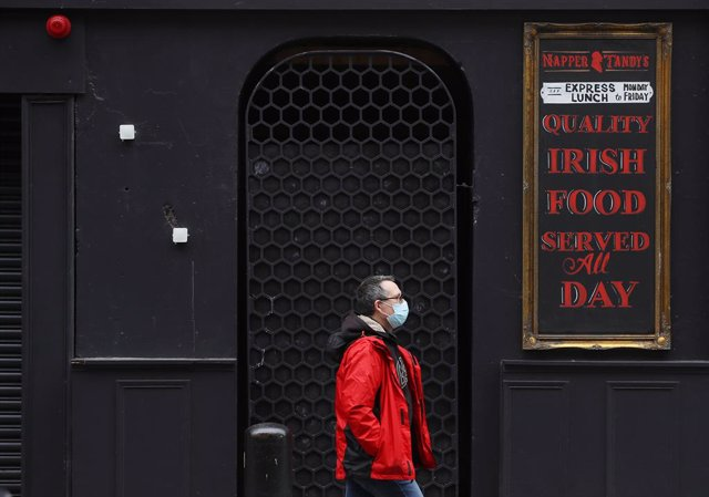 18 December 2020, Ireland, Dublin: A man passes by a closed pub in Dublin's city centre as restrictions have been eased in the lead up to the Christmas period. Photo: Brian Lawless/PA Wire/dpa