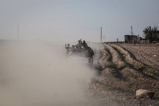 Milicianos del grupo rebelde Ejército Nacional Sirio, apoyado por Turquía, en un vehículo desplegado en una zona de combates contra fuerzas kurdas sirias