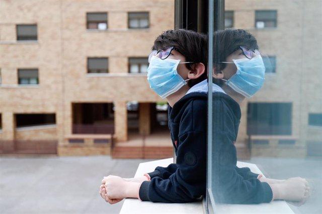 Un niño con una mascarilla se asoma a la ventana