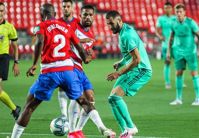 Karim Benzema of Real Madrid and Yangel Herrera of Granada CF fight for the ball during the spanish league, La Liga, football match played between Granada CF and Real Madrid CF at Nuevo Los Carmenes Stadium on July 13, 2020 in Granada, Spain.