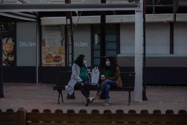 """Dos mujeres charlan sentadas en un banco, en Barcelona, Catalunya (España), a 21 de diciembre de 2020. Debido al incremento de la curva de la pandemia en Catalunya y ante """"la posible llegada de una tercera ola que incremente el nivel de presión sobre los"""