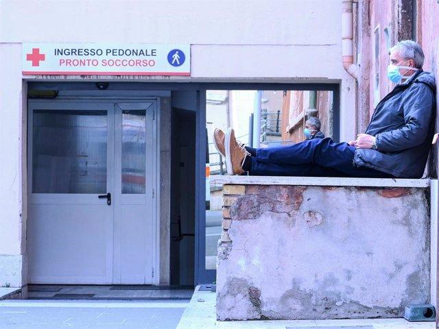 Un hombre con mascarilla espera a la puerta de un hospital en Roma durante la crisis del coronavirus
